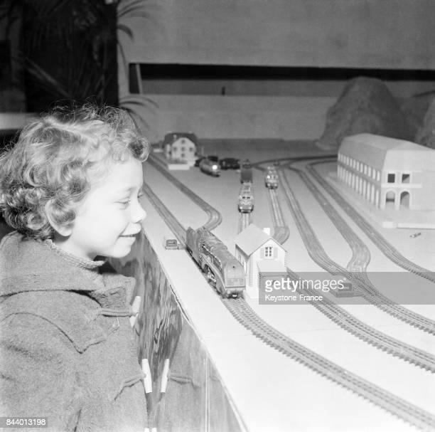 Un enfant regarde avec bonheur un circuit de train à Paris France le 10 décembre 1955
