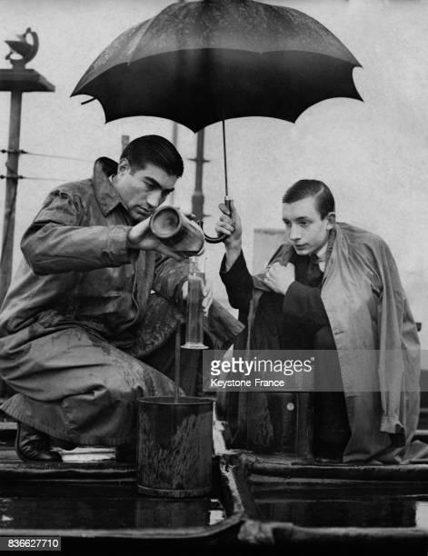 Un expert de l'entreprise Negretti et Zambra analyse la quantité d'eau tombée sur le toit d'un immeuble tandis qu'un homme l'abrite sous un parapluie...