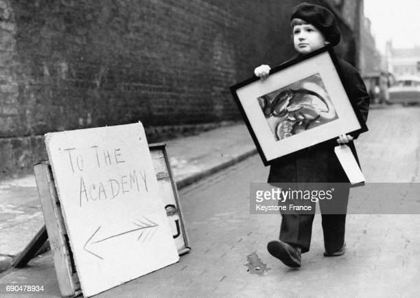 Un garçonnet de trois ans porte le tableau peint par sa mère à la Royal Academy le 21 mars 1952 à Londres RoyaumeUni