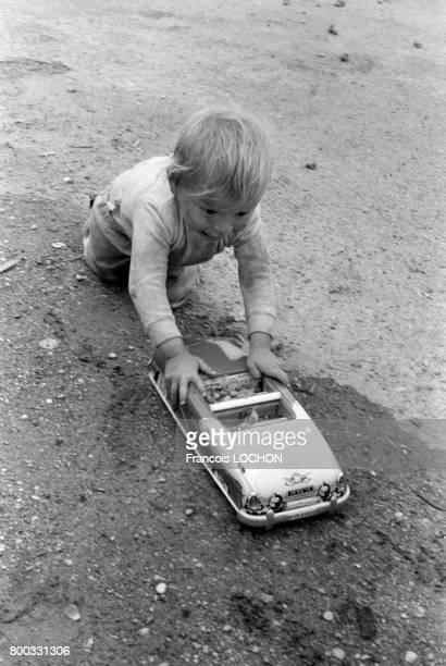 Un garçonnet gitan jouant avec une voiture miniature en 1973 à Reims France