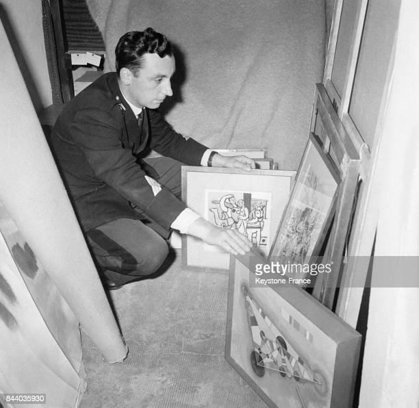 Un gendarme de la brigade d'Antibes montrent les tableaux volés et retrouvés dans une voiture à Antibes France le 15 avril 1961