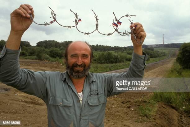 Un homme brandit un morceau de fil de fer barbele a la frontiere avec l'Allemagne en juillet 1990 a Karlovy Vary Republique Tcheque