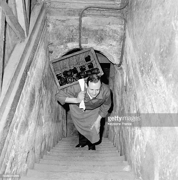Un homme chargé de bouteilles remonte l'escalier de la cave du restaurant 'Drouant' circa 1960 à Paris France