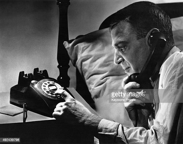 Un homme compose un numero sur le telephone mis au point par les laboratoires Bell et produit par la Western Electric Company et qui comporte une...