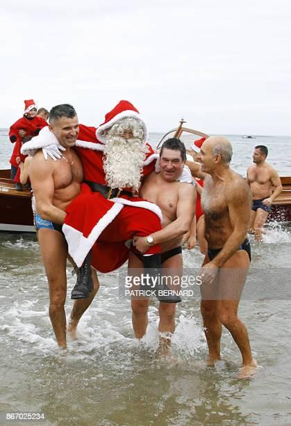 Un homme déguisé en père Noël est porté par les nageurs du traditionel bain de Noël à son arrivée sur la plage d'Arcachon le 17 décembre 2005 où il...