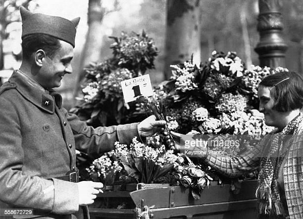 Un homme en uniforme militaire achète un bouquet de muguet poru le 1er mai à une marchande dans la rue en France