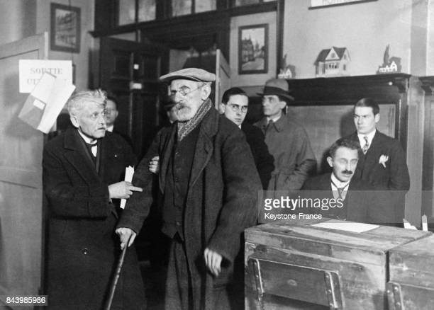 Un homme invalide arrive dans un bureau de vote lors des élections de la nouvelle Chambre et du Sénat en 1932 en Belgique