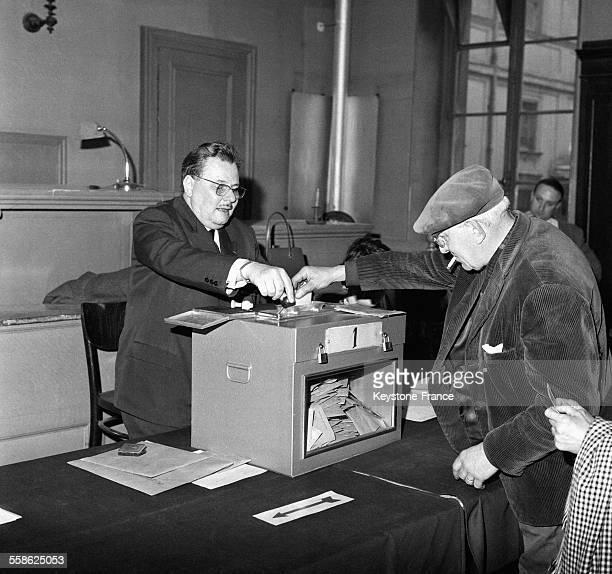 Un homme met son bulletin de vote dans l'urne transparente lors d'une election municipale dans un bureau de vote du 17eme arrondissement le 14 mars...