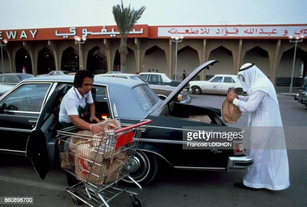 Un homme remplit le coffre arrière de sa voiture aprés avoir fait ses courses dans un centre commercial en avril 1980 en Arabie saoudite