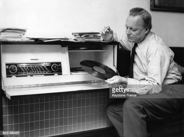 Un homme tenant un mégot de cigarette à la main hésite sur le choix du disque vinyle qu'il va écouter sur son tournedisque