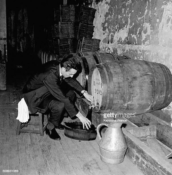 Un homme tire le vin d'un fût dans la cave du restaurant 'Drouant' circa 1960 à Paris France