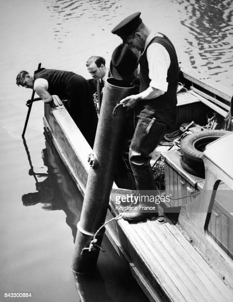 Un inspecteur de police sur un bateau regarde à travers un télescope sous marin le fond de la rivière à la recherche de disparues à Teddington...