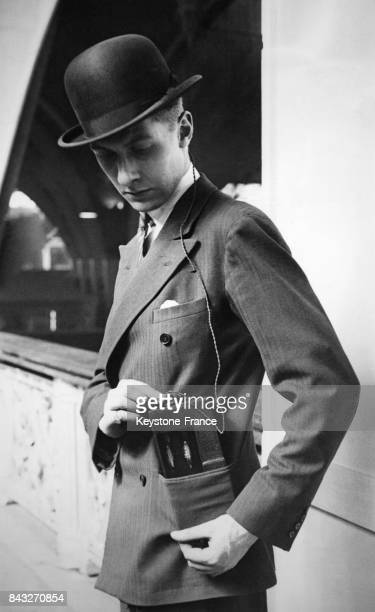 Un jeune homme fait la démonstration d'une radio portative intégrée dans un chapeau au Radio Show à l'Olympia circa 1930 à Londres RoyaumeUni