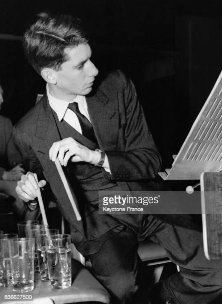 Un jeune homme John Warrack frappe des verres avec des baguettes de bois lors d'un concert organisé par les London Friends of Music au Royal Festival...