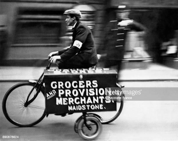 Un jeune homme sur un vélo de livraison est encouragé par un policier lors de la course du meilleur garçoncoursier le 7 octobre 1931 à Maidstone...
