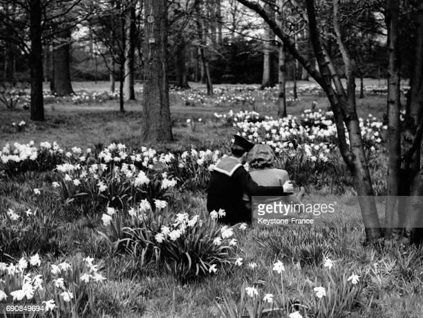 Un jeune marin enlace sa fiancée assis parmi les fleurs dans les jardins botaniques royaux de Kew à Londres RoyaumeUni