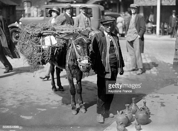 Un marchand de muguet espagnol avec son âne à Paris France le 1 mai 1931