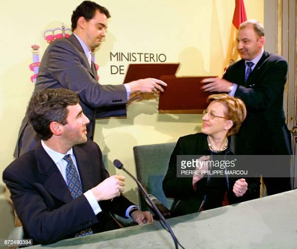 Un officiel espagnol échange avec un officiel français les versions de la déclaration commune francoespagnole sous les yeux de la ministre de la...