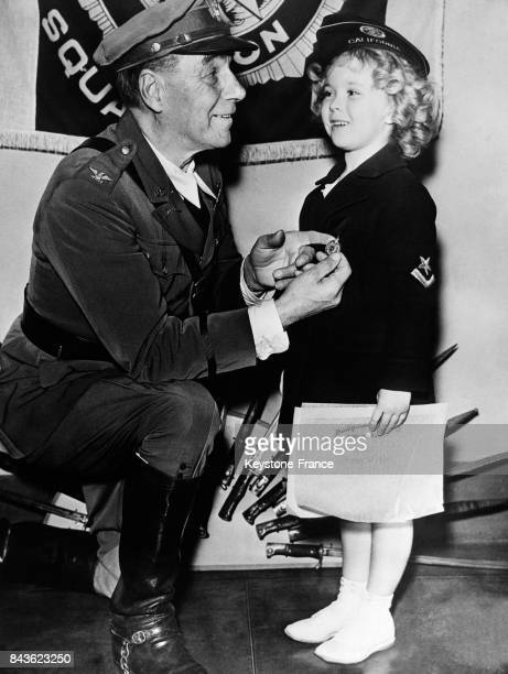 Un officier américain remet l'insigne de 'colonel de l'American Legion' à la très jeune actrice Shirley Temple lors d'une cérémonie à Hollywood le...