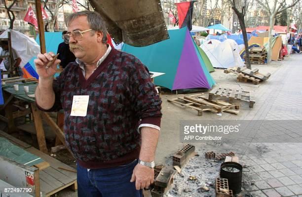 Un ouvrier en grève de l'entreprise espagnole de télécommunications Sintel fume un cigare 13 février 2001 sur l'avenue Castellana à Madrid Quelque...