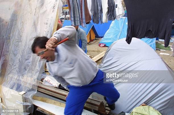 Un ouvrier en grève de l'entreprise espagnole de télécommunications Sintel consolide sa tente le 13 février 2001 sur l'avenue Castellana à Madrid...