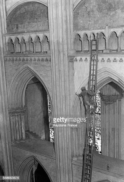Un ouvrier nettoyant une partie de la cathédrale au moyen d'un aspirateur à Rouen France le 11 mars 1931