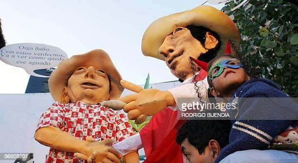 Un padre con su hija pasan junto a monigotes de un carro alegorico en una calle del centro de Quito el 31 de diciembre de 2005 Como es tradicional en...
