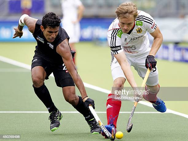Un Panchia of New Zealand fights for the ball with Linus Butt of Germany during a stage match between New Zealand and Germany in the men's tournament...