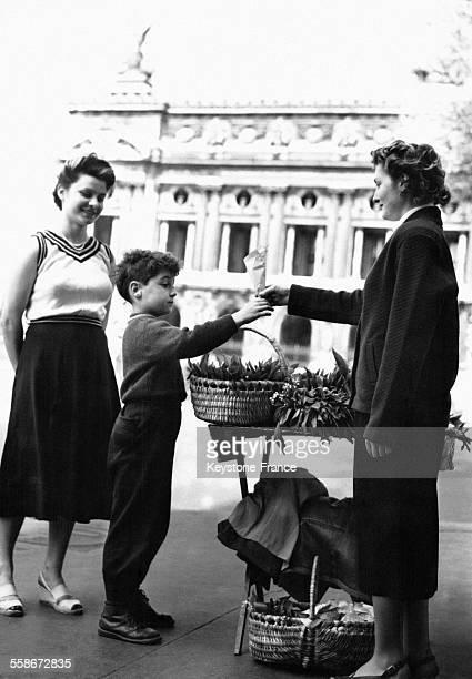 Un petit garçon achète un bouquet de muguet à une vendeuse sur la place de l'Opéra le 1er mai 1955 à Paris France