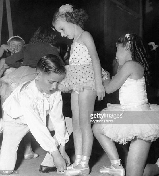 Un petit garçon aide une petite ballerine à serrer ses chaussons de danse avant un concours de danse à la Gaieté Lyrique le 11 octobre 1952 à Paris...