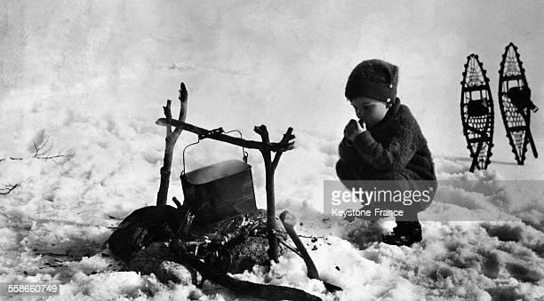 Un petit garçon dans les montagnes fait cuire son déjeuner et se réchauffe les mains à Chamonix France le 27 janvier 1931