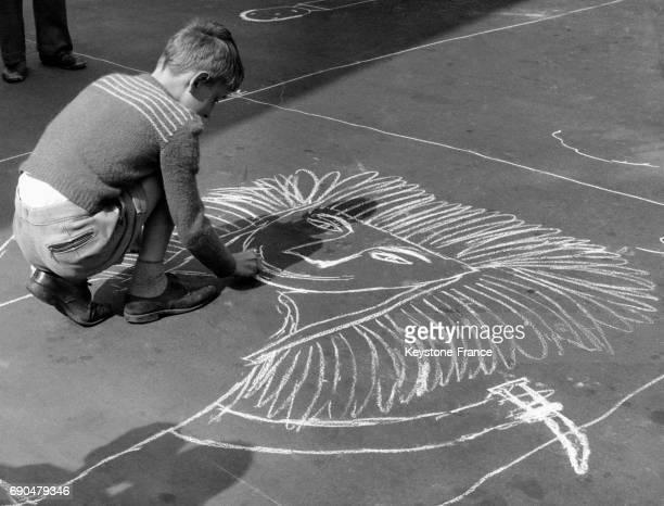 Un petit garçon dessine un lion à la craie sur le sol pendant les vacances d'été à Amsterdam PaysBas