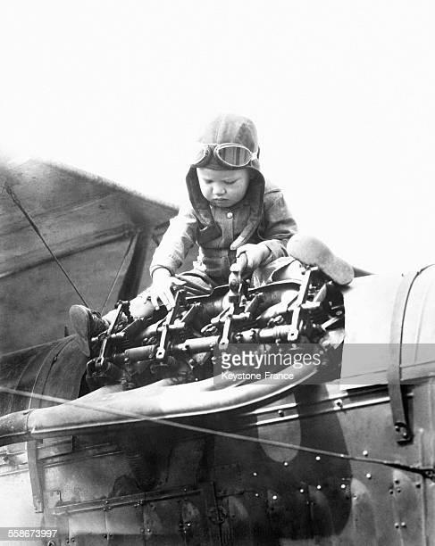 Un petit garçon porte un casque de pilote sur un avion pour la série 'Les Petites Canailles' d'Hal Roach circa 1930 en Californie