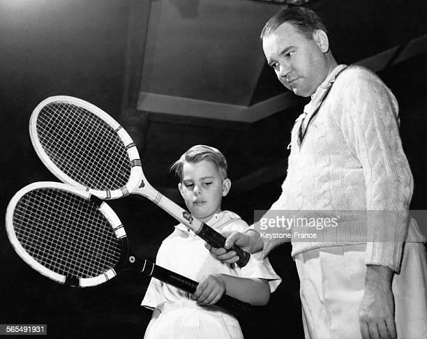 Un professeur de tennis montrant à son élève comment bien tenir sa raquette