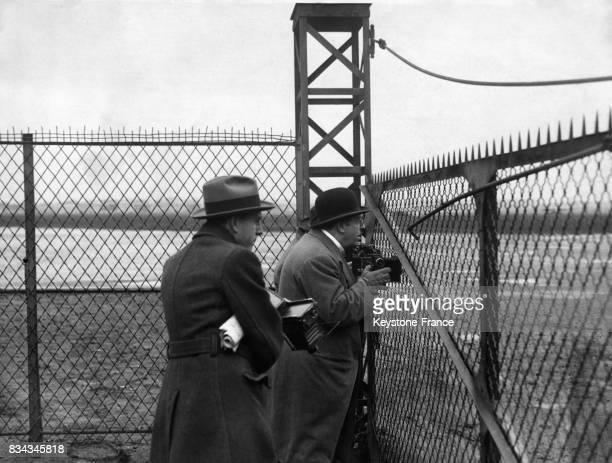 Un reporterphotographe derrière les grilles du Bourget essaie de prendre un cliché du Prince de Galles au Bourget France le 29 avril 1931