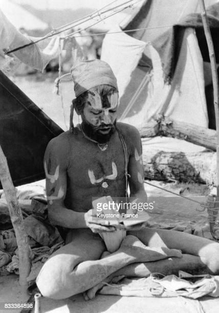 Un sadhu enduit de bouse de vache de cendres et d'une pâte blanche épaisse porte sur le front un signe blanc et rouge symbolisant le sexe féminin et...