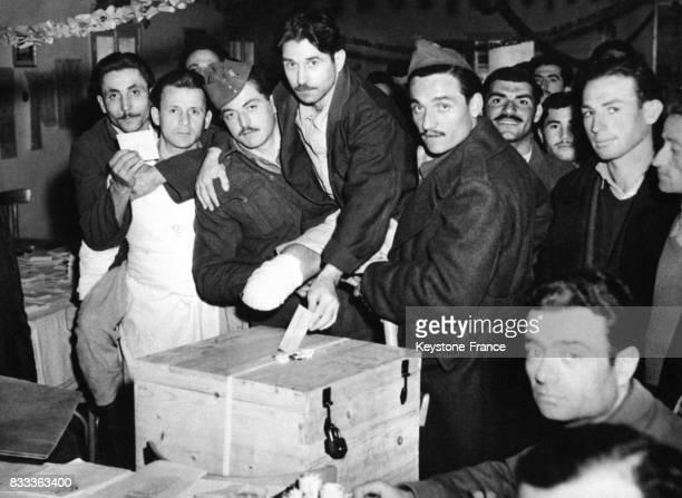 Un soldat amputé de la jambe se fait porter par ses camarades pour glisser son bulletin de vote dans l'urne à Athènes Grèce le 8 mars 1950