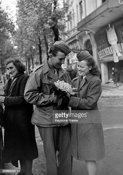 Un soldat américain offre du muguet à une jeune femme militaire à Paris France le 1er mai 1945