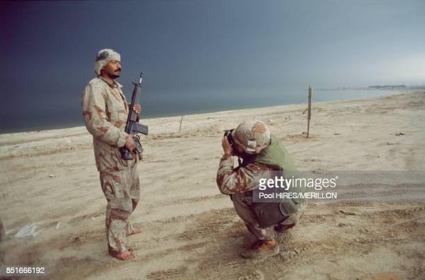 Un soldat américain photographie un militaire saoudien lors de la 1ère guerre du golfe à El Khafji le 23 février 1991 Koweït