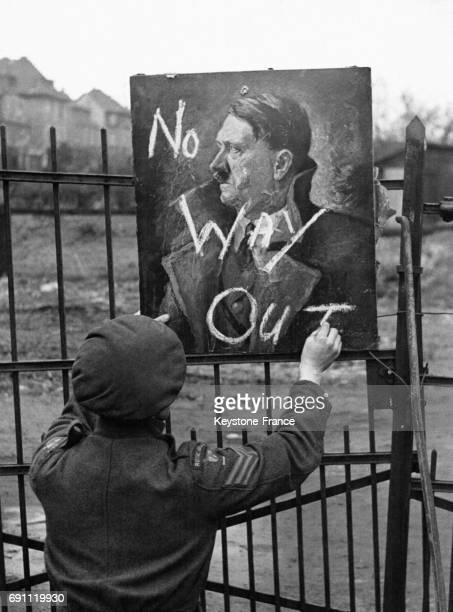 Un soldat britannique écrit à la craie avec humour 'Pas de sortie' sur un portrait d'Adolf Hitler indiquant aux soldats que l'entrée du QG militaire...