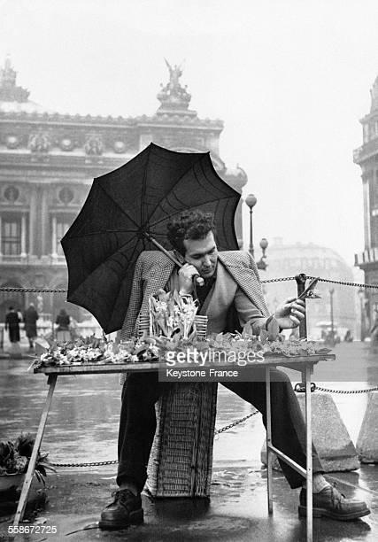 Un vendeur de muguet s'abrite sous son parapluie lors d'un averse place de l'Opéra le 1er mai 1951 à Paris France