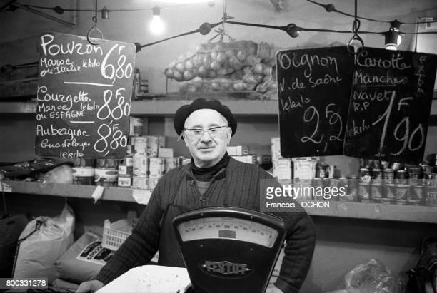 Un vendeur du marché Secrétan avec derrière lui le prix des légumes affiché sur des ardoises le 19 février 1976 à Paris France