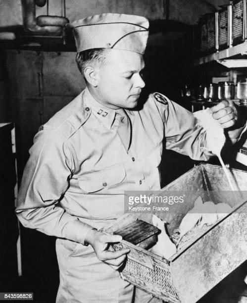 Un vétérinaire de l'armée américaine examine de petites souris blanches qui seront embarquées pour les atoll Bikini et utilisées comme cobayes pour...