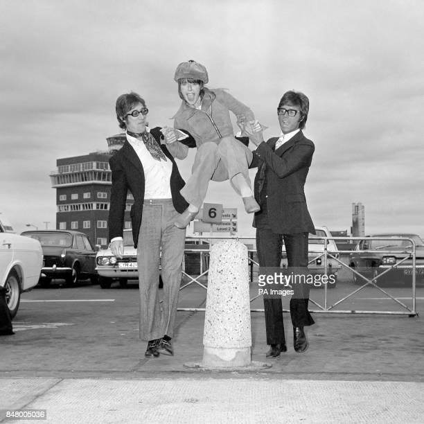 Una Stubbs leaps over a bollard at Heathrow Airport with the assistance of fellow entertainers Hank Marvin left and Cliff Richard The three were...