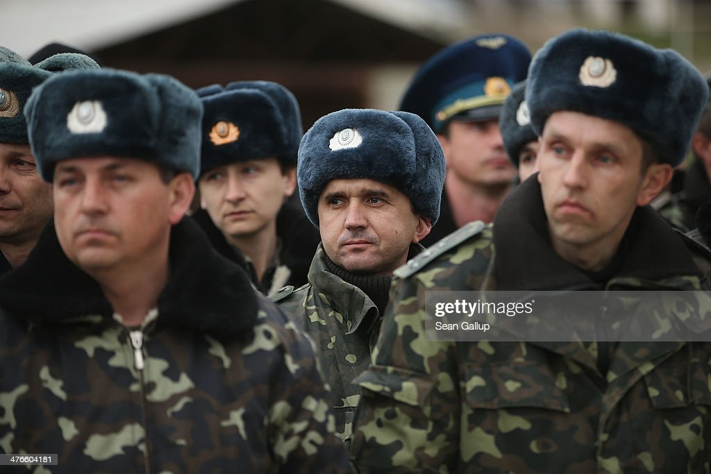 Unarmed Ukrainian troops listen to their commander speak before they marched to confront soldiers under Russian command occupying the nearby Belbek airfield in Crimea on March 4, 2014 in Lubimovka, Ukraine. The Ukrainians are stationed at their garrison nearby, and after spending a tense night anticipating a Russian attack following the expiration of a Russian deadline to surrender, in which family members of troops spent the night at the garrison gate in support of the soldiers, their commander Colonel Yuli Mamchor announced his bold plan this morning to retake the airfield by confronting the Russian-lead soldiers unarmed. The Russian-lead troops fired their weapons into the air but then granted Mamchor the beginning of negotiations with their commander. Russian-lead troops have blockaded a number of Ukrainian military bases across Crimea.