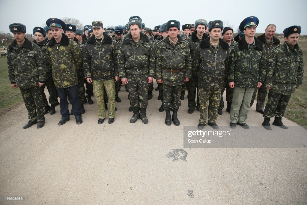 Unarmed Ukrainian troops stand at a road on the Belbek airfield after they confronted soldiers under Russian command occupying the base in Crimea on March 4, 2014 in Lubimovka, Ukraine. The Ukrainians are stationed at their garrison nearby, and after spending a tense night anticipating a Russian attack following the expiration of a Russian deadline to surrender, in which family members of troops spent the night at the garrison gate in support of the soldiers, their commander Colonel Yuli Mamchor announced his bold plan this morning to retake the airfield by confronting the Russian-lead soldiers unarmed. The Russian-lead troops fired their weapons into the air but then granted Mamchor the beginning of negotiations with their commander. Russian-lead troops have blockaded a number of Ukrainian military bases across Crimea.