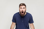 Unbelievable news! Young adult crazy man with opened mouth looking at camera. Studio shot, gray background