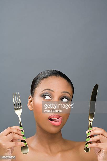Uncertain looking woman holding cutlery