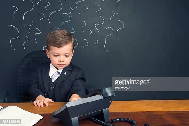 Incertitude concept. Jeune garçon assis derrière le bureau