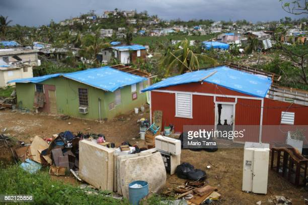Uncollected debris stand near damaged homes in an area without electricity on October 15 2017 in San Isidro Puerto Rico Puerto Rico is suffering...